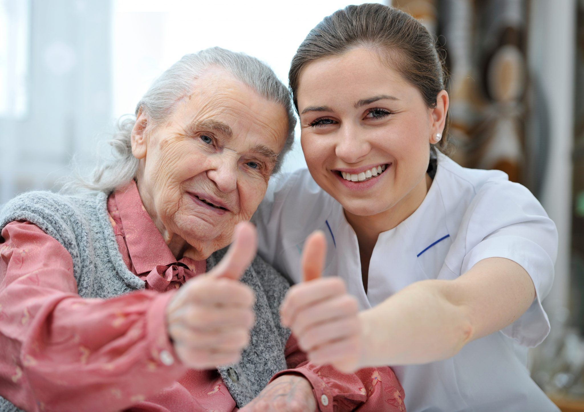Apex Care Homes Senior woman and female nurse are showing thumbs up